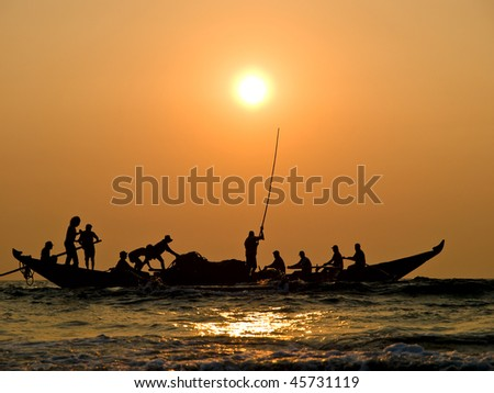 Fishers' boat in sunset - stock photo