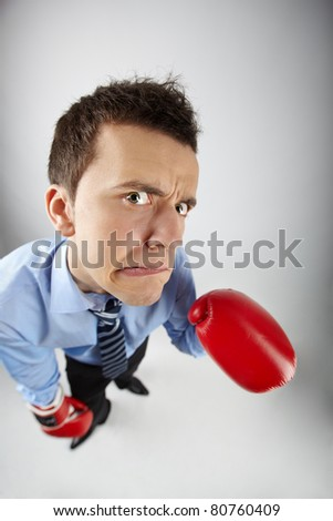 Fisheye of displeased businessman in boxing gloves looking at camera - stock photo