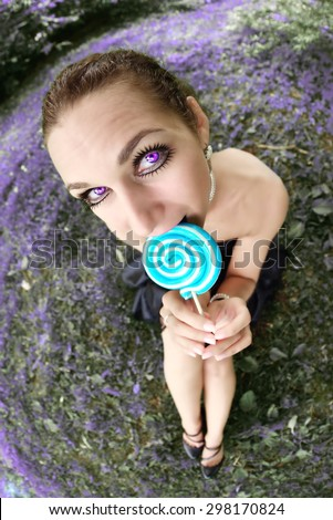 Fisheye portrait of beautiful woman with lollipop candy sitting on meadow - stock photo