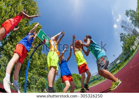 Fisheye view from below of teens during basketball - stock photo