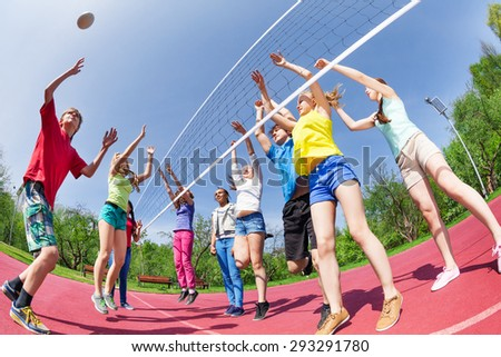 Fisheye view of teens playing volleyball on ground - stock photo