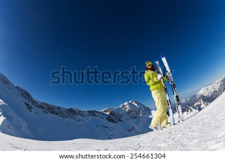 Fisheye view of young woman in mask holding ski - stock photo