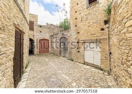 Fisheye view on vanishing medieval narrow pavement street passage with stonemasonry building. Pano Lefkara, Cyprus.  - stock photo