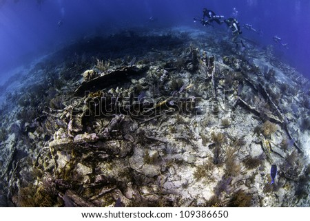 fisheye view over a coral reef with an old shipwreck scattered throughout. Located in the John Pennekamp State Park in Key Largo, Florida. - stock photo