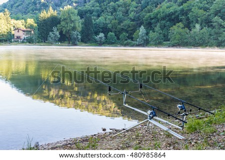Fishing adventures.  Carpfishing rods propped on a rod pod with two bite alarms, as a background a lake with low mist
