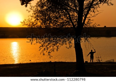 fishing at the sunset, man feeding the fish at the sunset, landscape image
