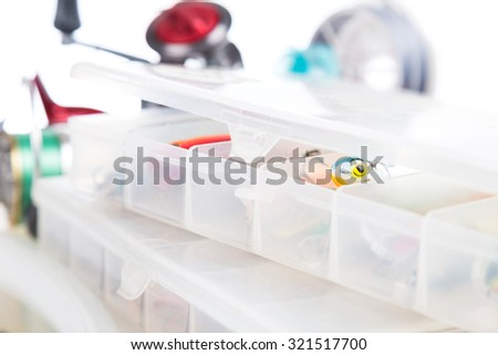 fishing baits and lure in transparent plastic storage boxes on bright white background. for design advertising or publication