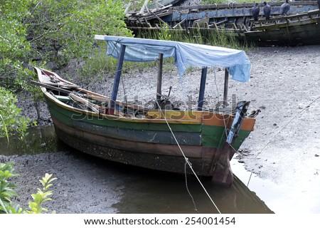 fishing boat abandoned in brazilian coast - stock photo
