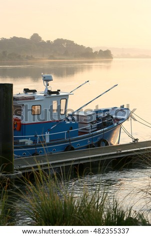 Fishing boat anchored on the banks of a river at sunrise in the basque country