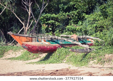 Fishing boat and a fragment of a fishing net on a tropical beach with mangrove in the background - stock photo