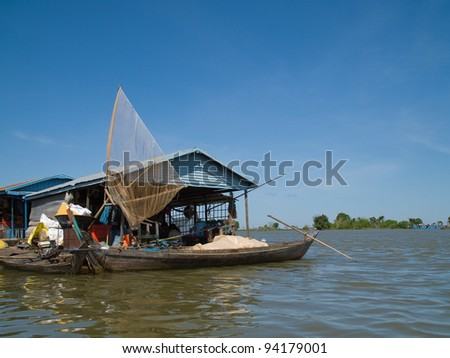 Fishing boat and net at Vietnamese floating village on Tonle Sap river at Kampong Chhnang in Cambodia. - stock photo