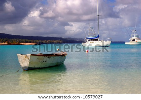 fishing boat and yachts docked at a tropical harbor