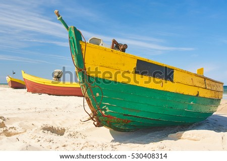 Fishing boat at baltic sea sandy beach with dramatic sky during summertime in Poland
