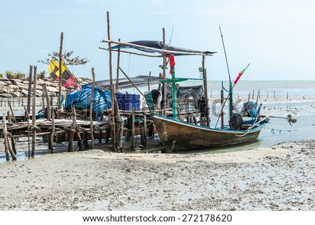 Fishing boat at low tide in the south of Thailand - stock photo