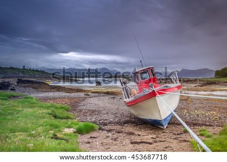 Fishing Boat at Low Tide on Scottish Coast of Isle of Skye - stock photo