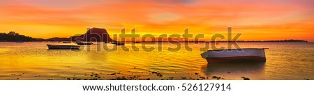 Fishing boat at sunset time. Le Morn Brabant on background. Mauritius. Panorama