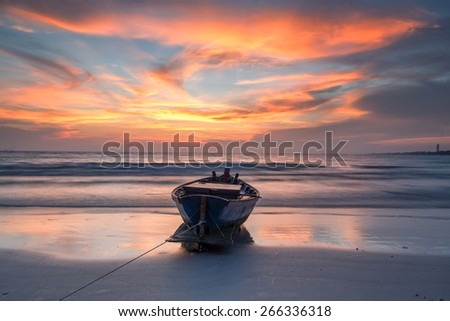 Fishing boat at the beach during sunset - stock photo