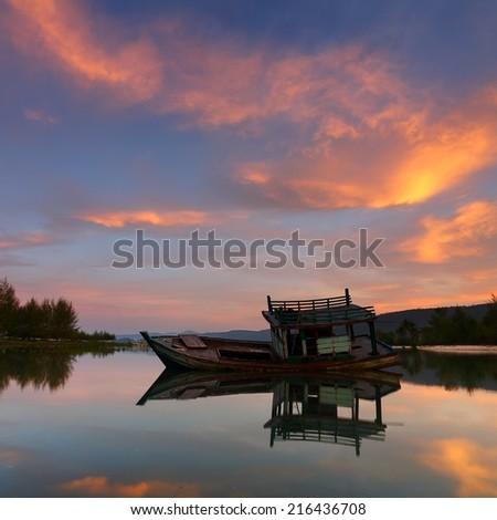 Fishing boat capsize in sunrise  - stock photo