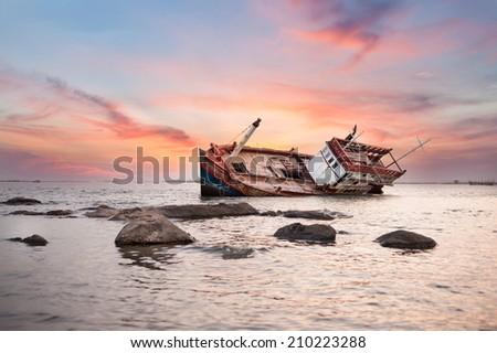 Fishing boat capsize sunset blackground - stock photo