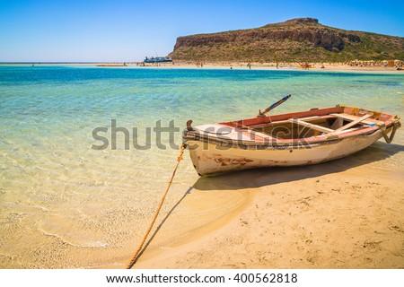 Fishing boat docked to coast on the beautiful beach of Crete, Greece - stock photo