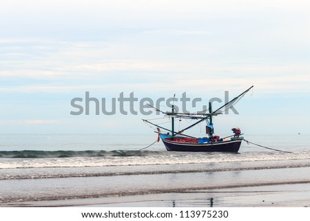 Fishing boat floating on the shore. - stock photo