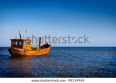 Fishing boat floating on the water, blue sea and sky with copyspace - stock photo