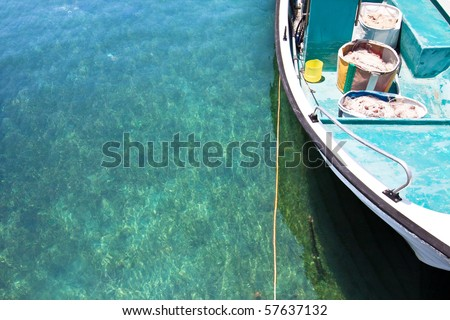 Fishing boat in crystal clear turquoise water - stock photo