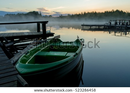 Fishing boat in foggy lake, Belarus, Summer