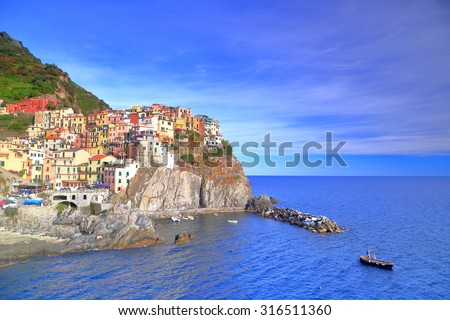 Fishing boat in front of the harbor and village of Manarola at nightfall, Cinque Terre, Italy - stock photo