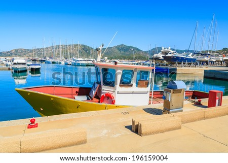 Fishing boat in harbour of Porto Giunco, Sardinia island, Italy - stock photo
