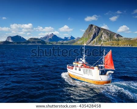 Fishing boat in Norway fjord - sea in lofoten nature. Norway finshing. Norway boat. Norway ocean. - stock photo