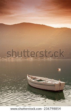 fishing boat in the bay at sunset - stock photo