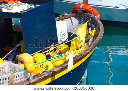 Fishing Boat in the Harbor - Liguria Italy / Blue and yellow small fishing boat with fishing equipment docked in port - Lerici, La Spezia, Liguria, Italy - stock photo