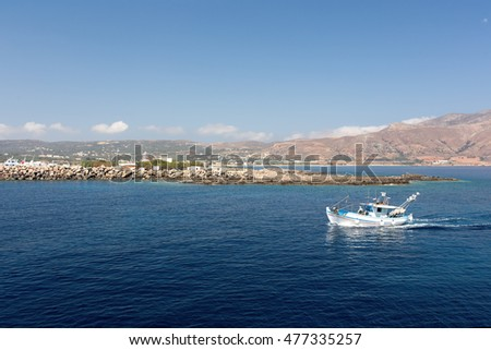 fishing boat in the sea on a background of mountains