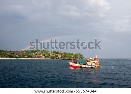 Fishing boat makes it way through the sea under the rainbow