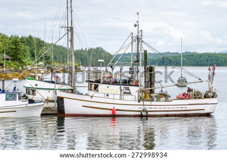 Fishing Boat Moored in Harbour on a Cloudy Day - stock photo