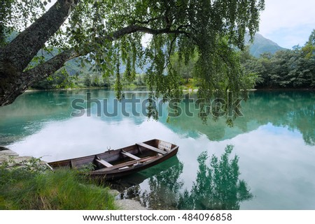 Fishing boat on a still green lake in Norway and mountains in background