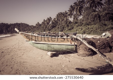 Fishing boat on a tropical beach with palm trees in the background. Vintage style beach background - stock photo
