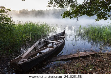 Fishing Boat on Foggy Lake at dusk