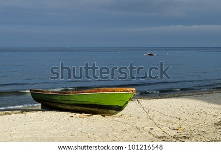 Fishing boat on sandy beach - stock photo
