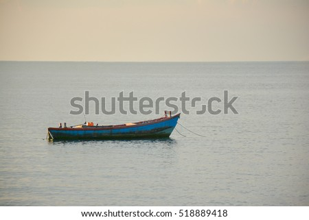 fishing boat on sea at sunset