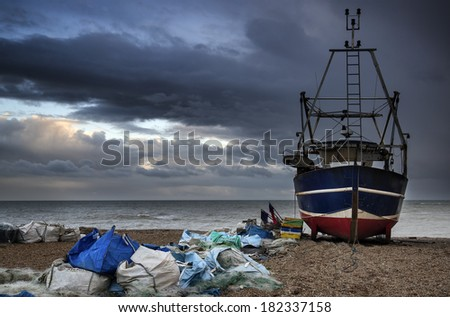 Fishing boat on shingle beach landscape with stormy sky - stock photo