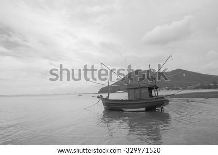 fishing boat on the beach after sea tide black and white tone at Bangsarey near Pattaya, Thailand - stock photo