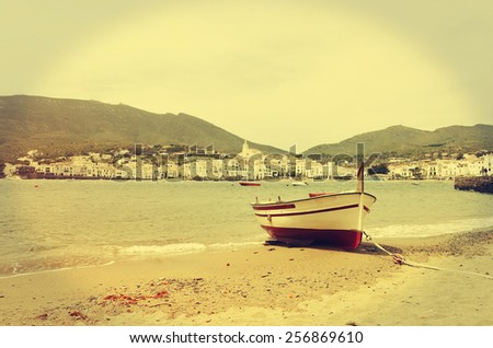 Fishing boat on the beach and the old Town in the background. Cadaques, Costa Brava, Catalonia, Spain. - stock photo