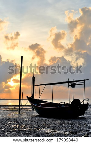 Fishing boat on the beach when sun rising up. Soft focus - stock photo