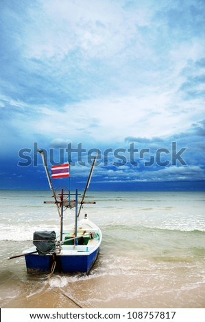 fishing boat on the beach with storm coming , Hua-Hin , Thailand