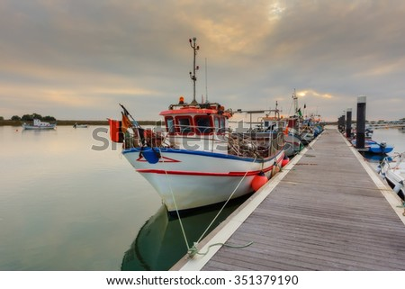 Fishing boat on the dock Portugal. Sunset in the sea. - stock photo