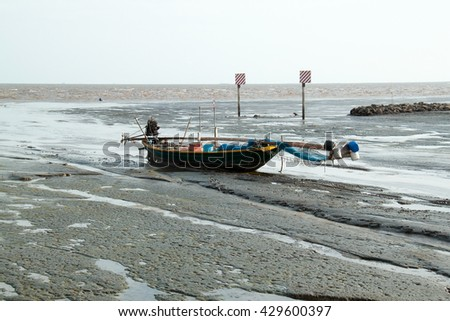 fishing boat on the sand when low tide