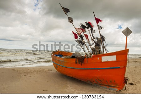 Fishing boat on the sandy beach in rainy day - Rewal, Poland, Baltic sea. - stock photo