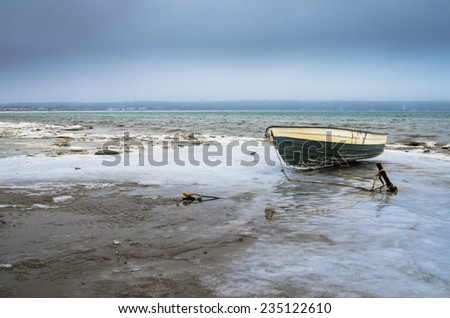 Fishing boat on the shore of the Baltic Sea. Winter landscape
